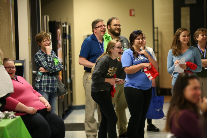 Moraine park students and staff laughing during balloon artist and comedian show