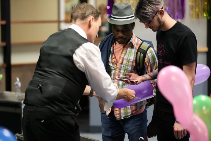 balloon artist talks with students