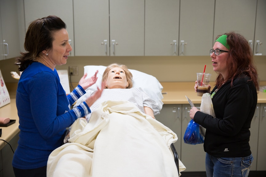 Nursing Instructor talking with women in lab at Moraine Park Open House