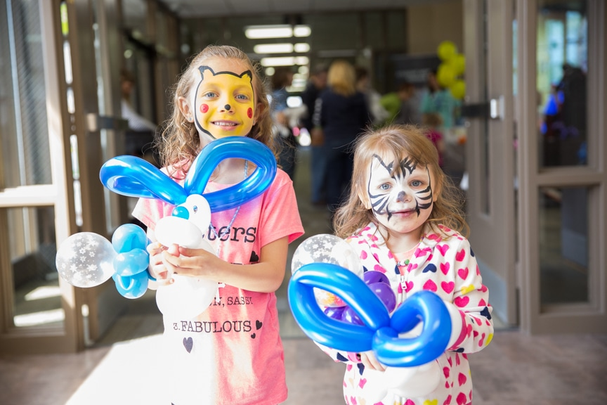 Two girls with face paint and balloons at Moraine Park Open House