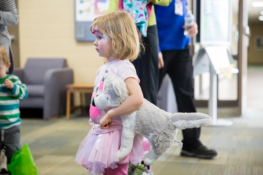 Little girl with face paint an a mascot wolf