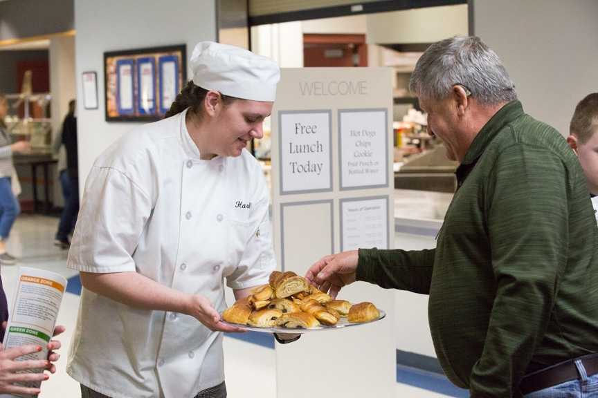Culinary student offering a crescent to man at Moraine Park Open House