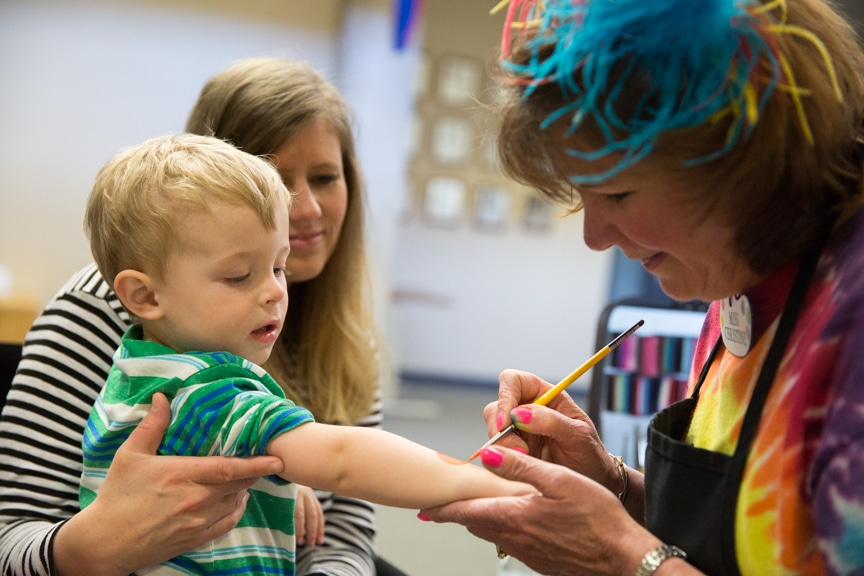 Dani Pantzlaff watches as her son gets his arm painted at Moraine Park Open House