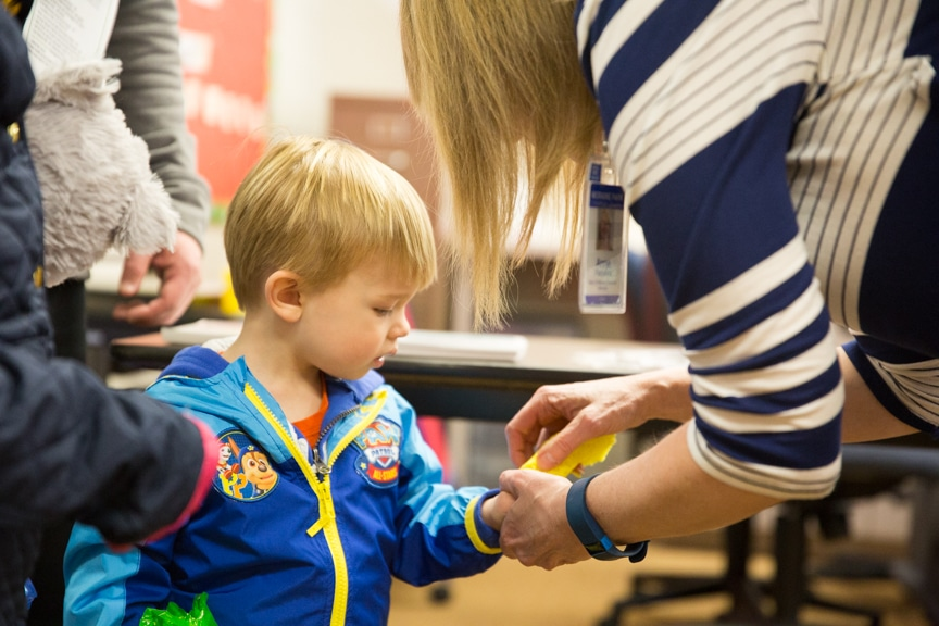 Little boy receiving an adhesive sticker on hand at Moraine Park Open House