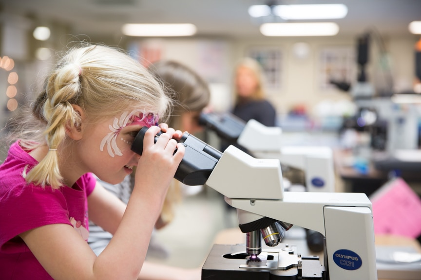 Olive Pantzlaff looking through microscope at Moraine Park Open House