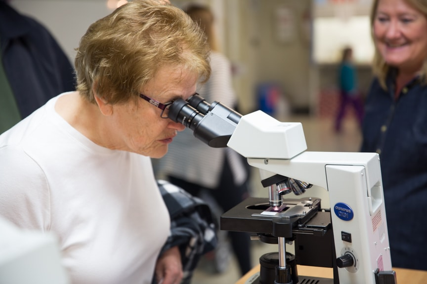 Woman looking through microscope at Moraine Park Open House