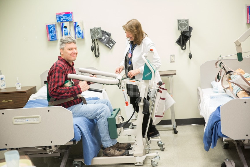 Ryan Flanigan experiencing bed lift machine in Nursing lab at Moraine Park Open House