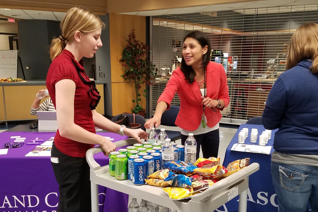 student reaches for soda can on cart at healthcare career fair