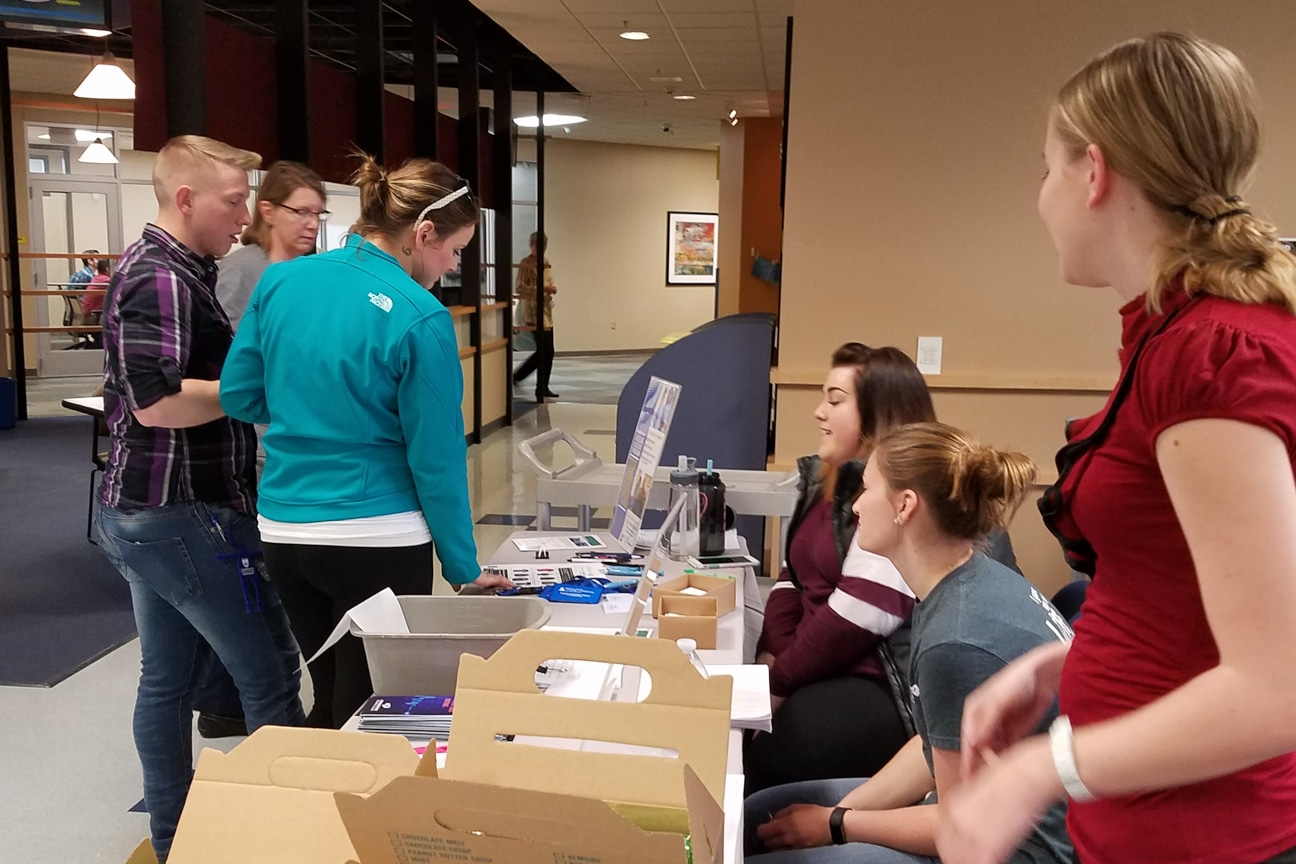 students stop by table at healthcare career fair