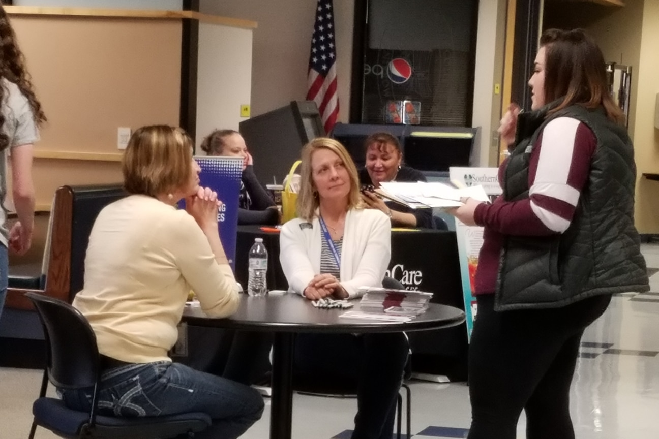student talks with staff at healthcare career fair