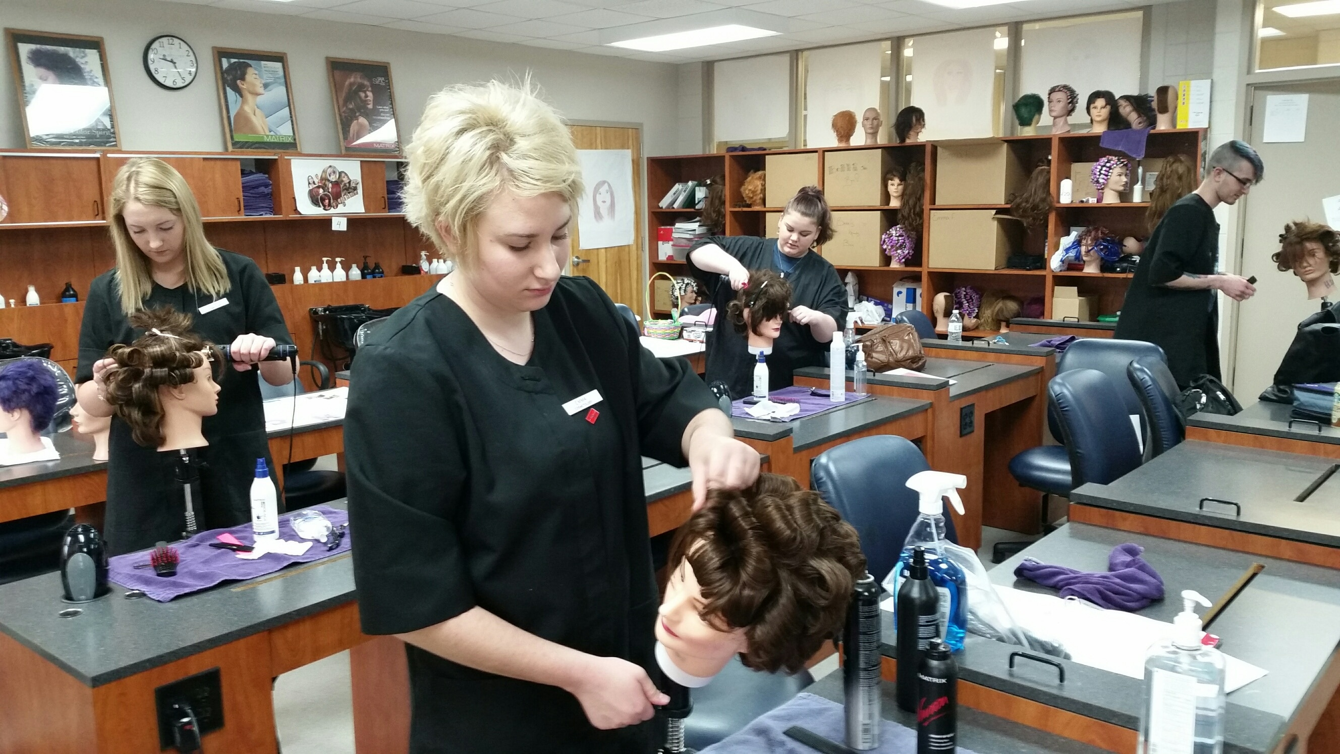 female student styles mannequin hair at moraine park