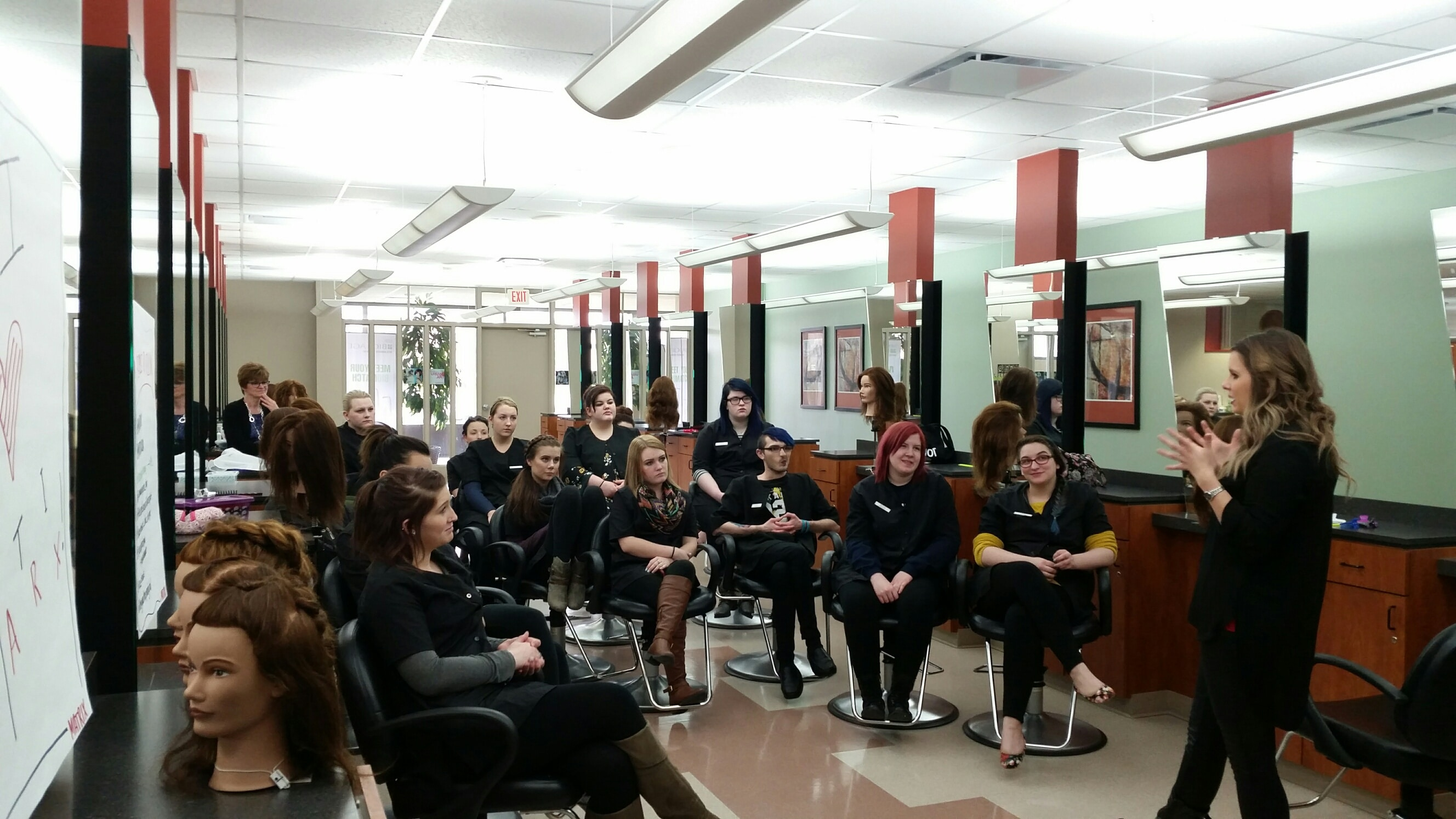 cosmetology students sit in chairs in salon while listening to speaker