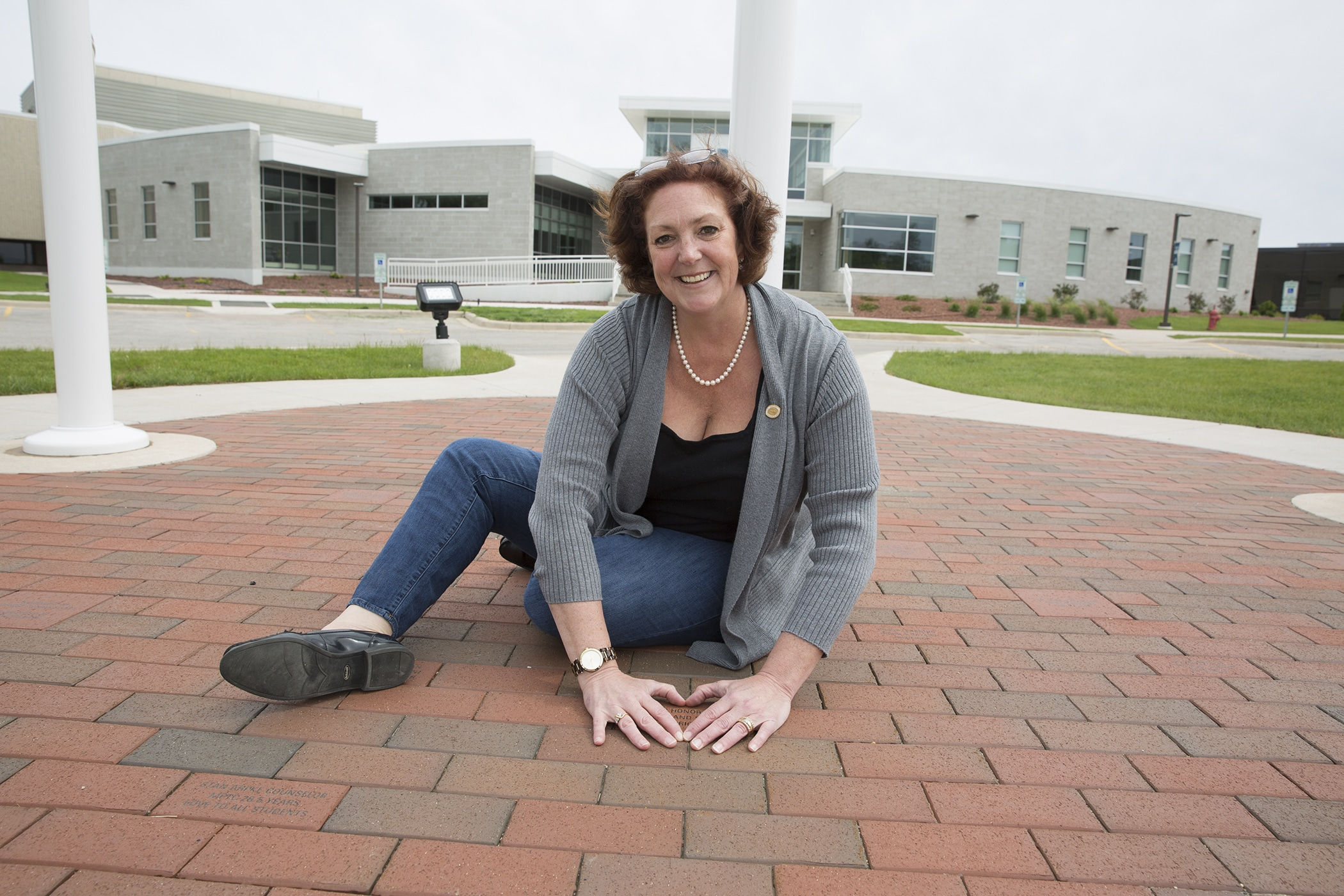 Heather Evenson makes a heart shape with her hands over a memorial brick outside of Moraine Park