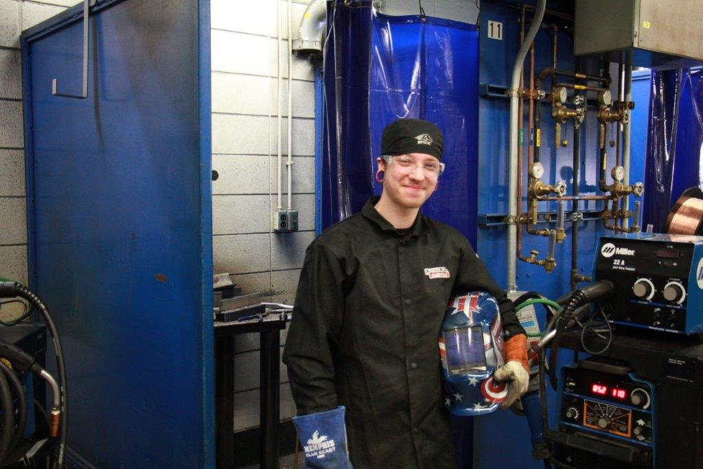 male student stands by welding area