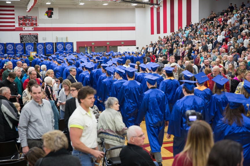 Row of graduates march down aisle