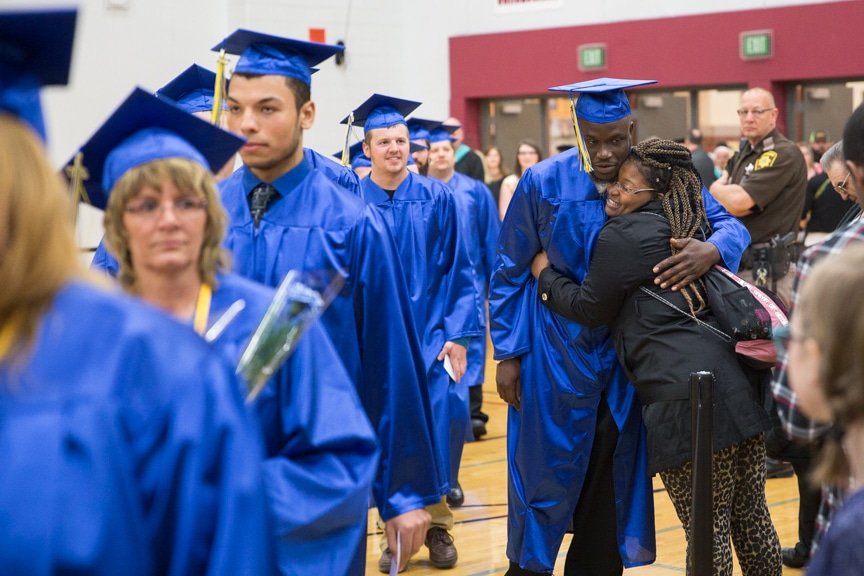 Male graduate recieves hug while walking down aisle at Moraine Park commencement ceremony