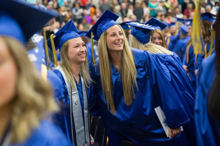 Two female graduates smile into crowd at Moraine Park commencement ceremony
