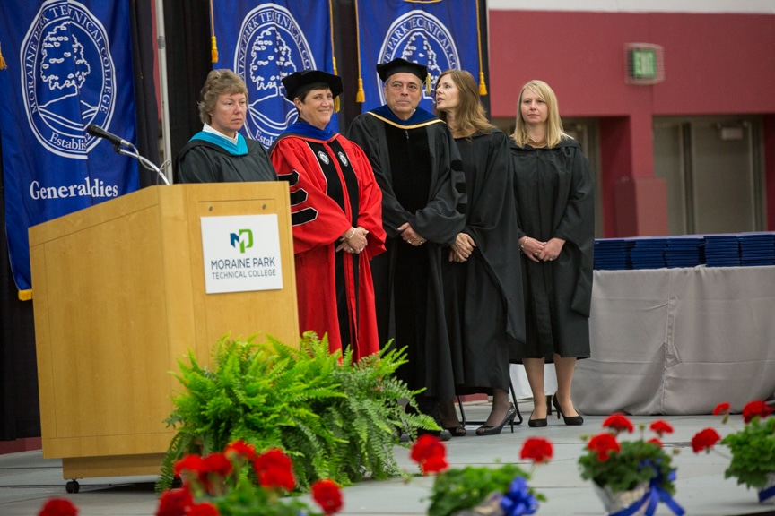 Distinguished guests at Moraine Park commencement ceremony stand near podium