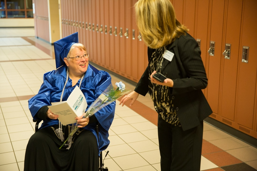 Staff member talks to graduate in wheelchair prior to Moraine Park commencement ceremony