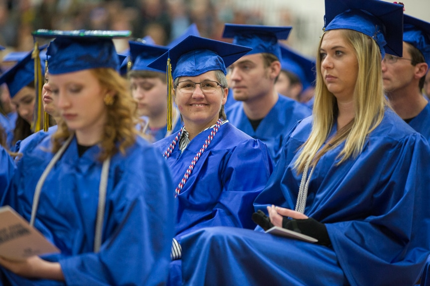 Female graduate smiles from crowd at Moraine Park commencement ceremony