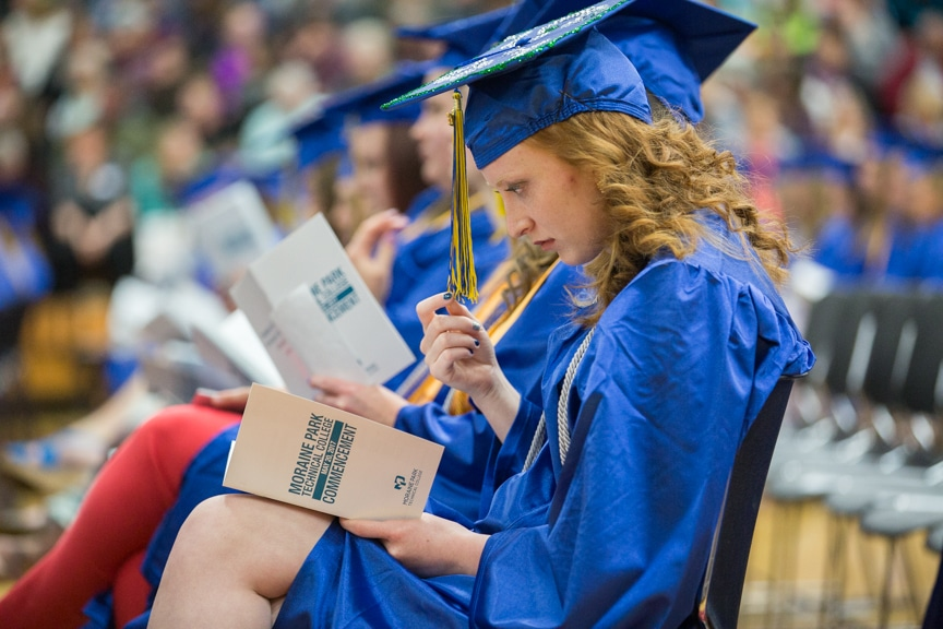 Female student looks down at program at Moraine Park commencement ceremony