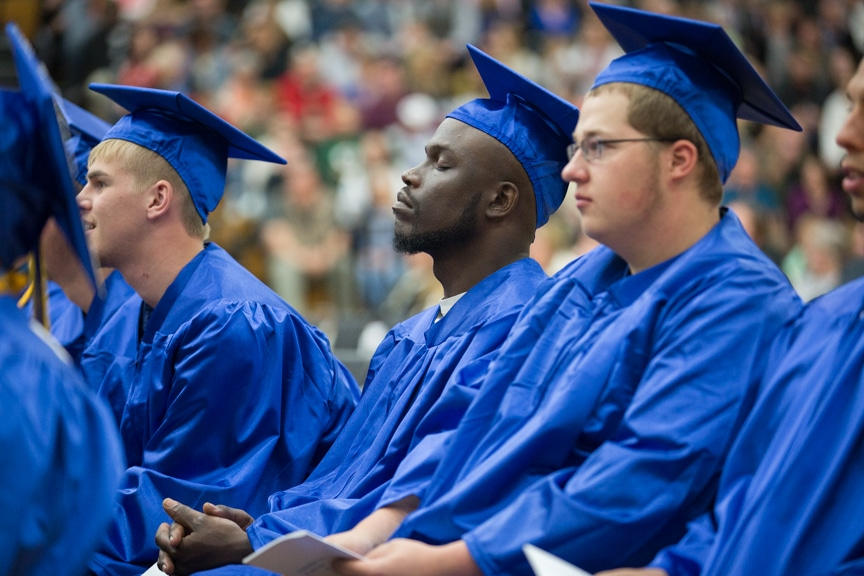 Male graduate listen to speeches stoically
