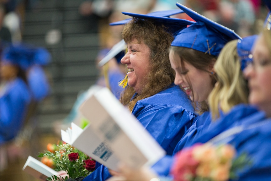 Female graduate smiles in crowd at Moraine Park commencement ceremony