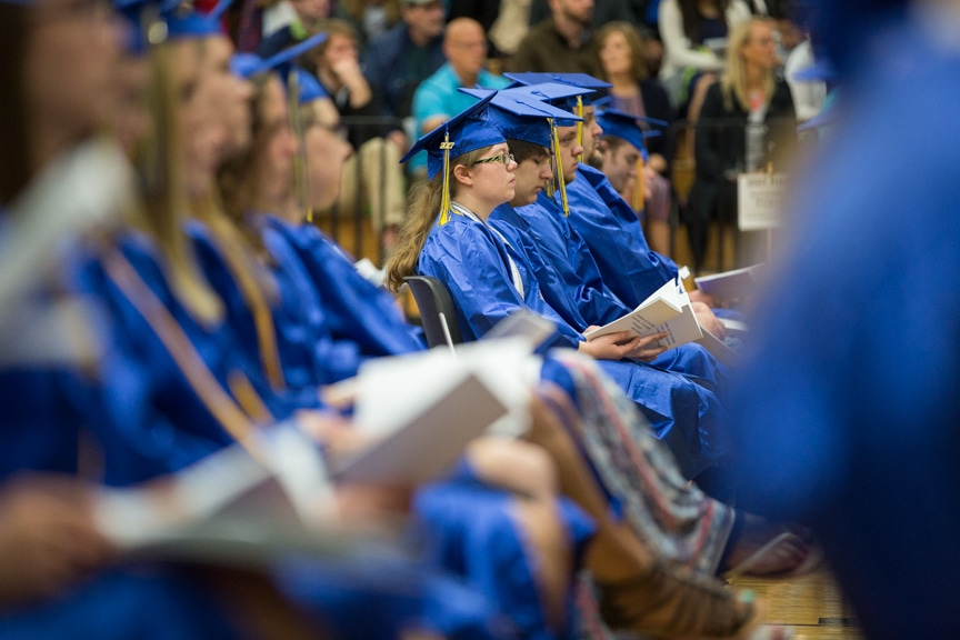 Row of graduates sit together at Moraine Park commencement ceremony