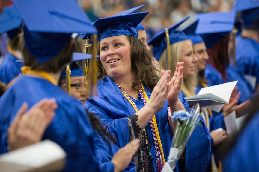Graduates clap hands at Gradutes sit at Moraine Park commencement ceremony
