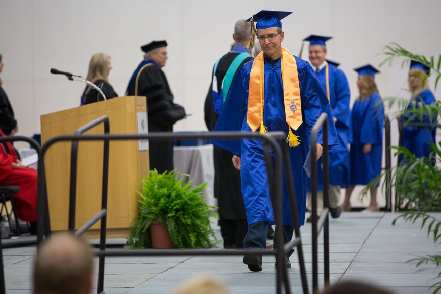 Graduates walk off stage after getting diplomas at Moraine Park commencement ceremony