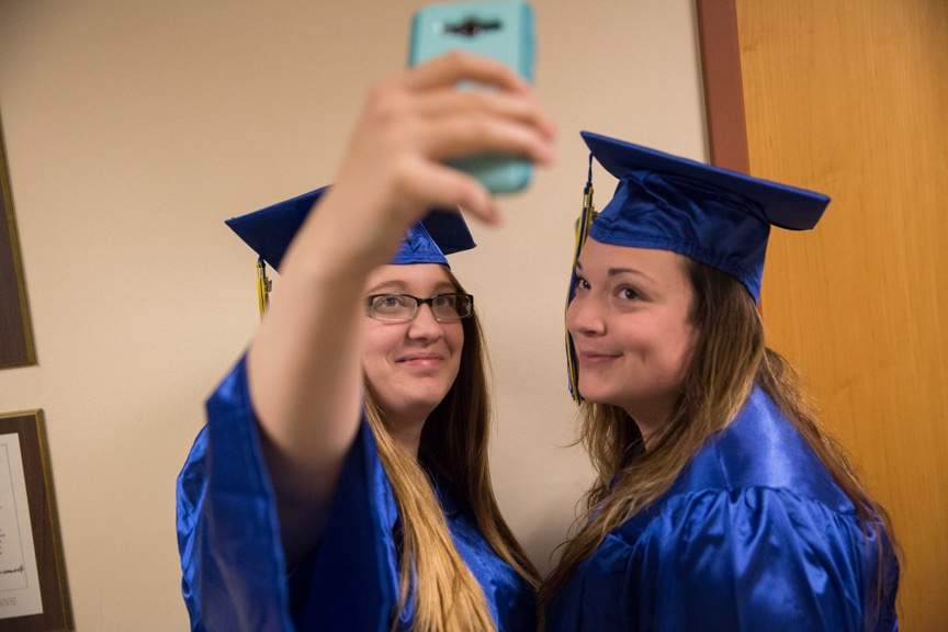Two female graduates pose for selfie at Moraine Park commencement ceremony