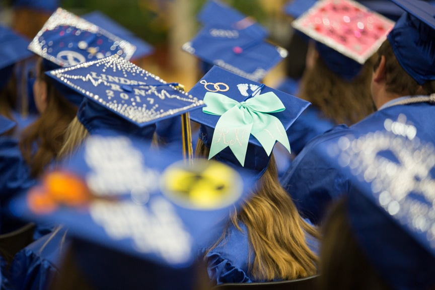 Top of graduate caps with bows and glittered messages