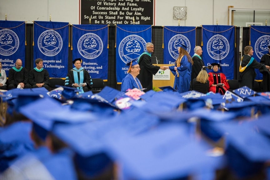 Female student recieves diploma at Moraine Park commencement ceremony