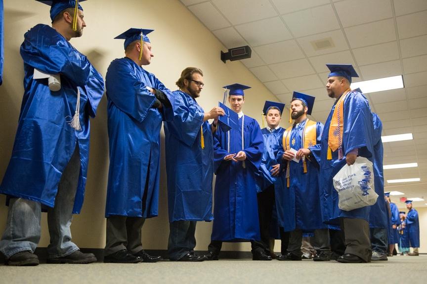 Row of graduates wait in hallway along hallway wall