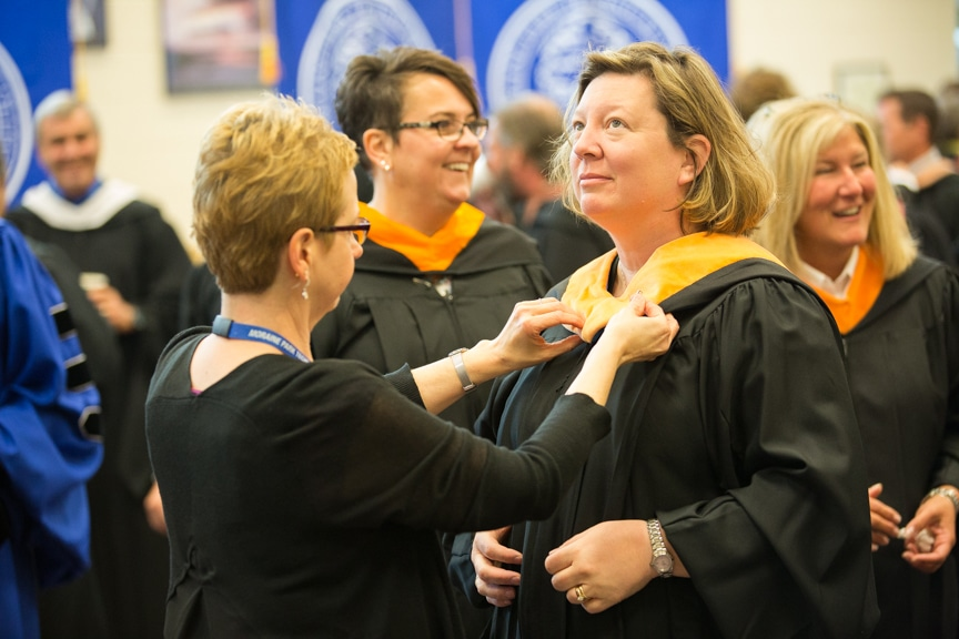 Staff putting on gowns prior to Moraine Park commencement ceremony