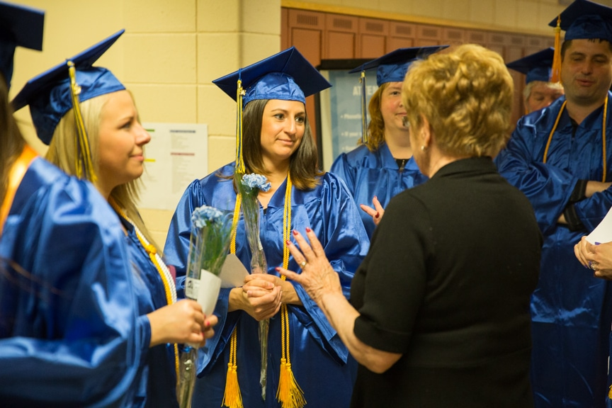 Graduates and staff talking before Moraine Park commencement ceremony