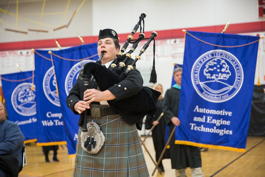 Bagpipe player marches down aisle at Moraine Park commencement ceremony