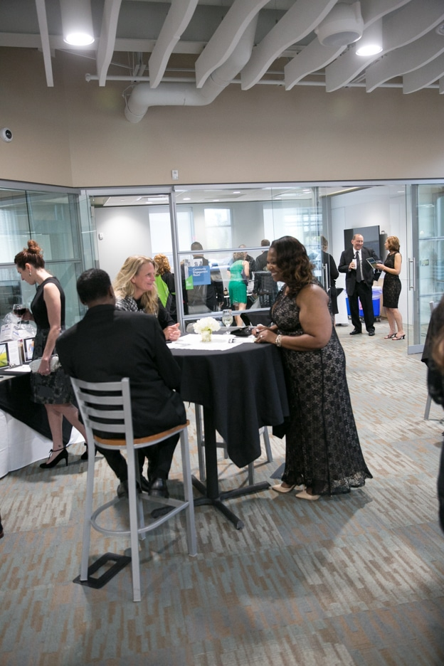 Gourmet dinner attendees at tables.