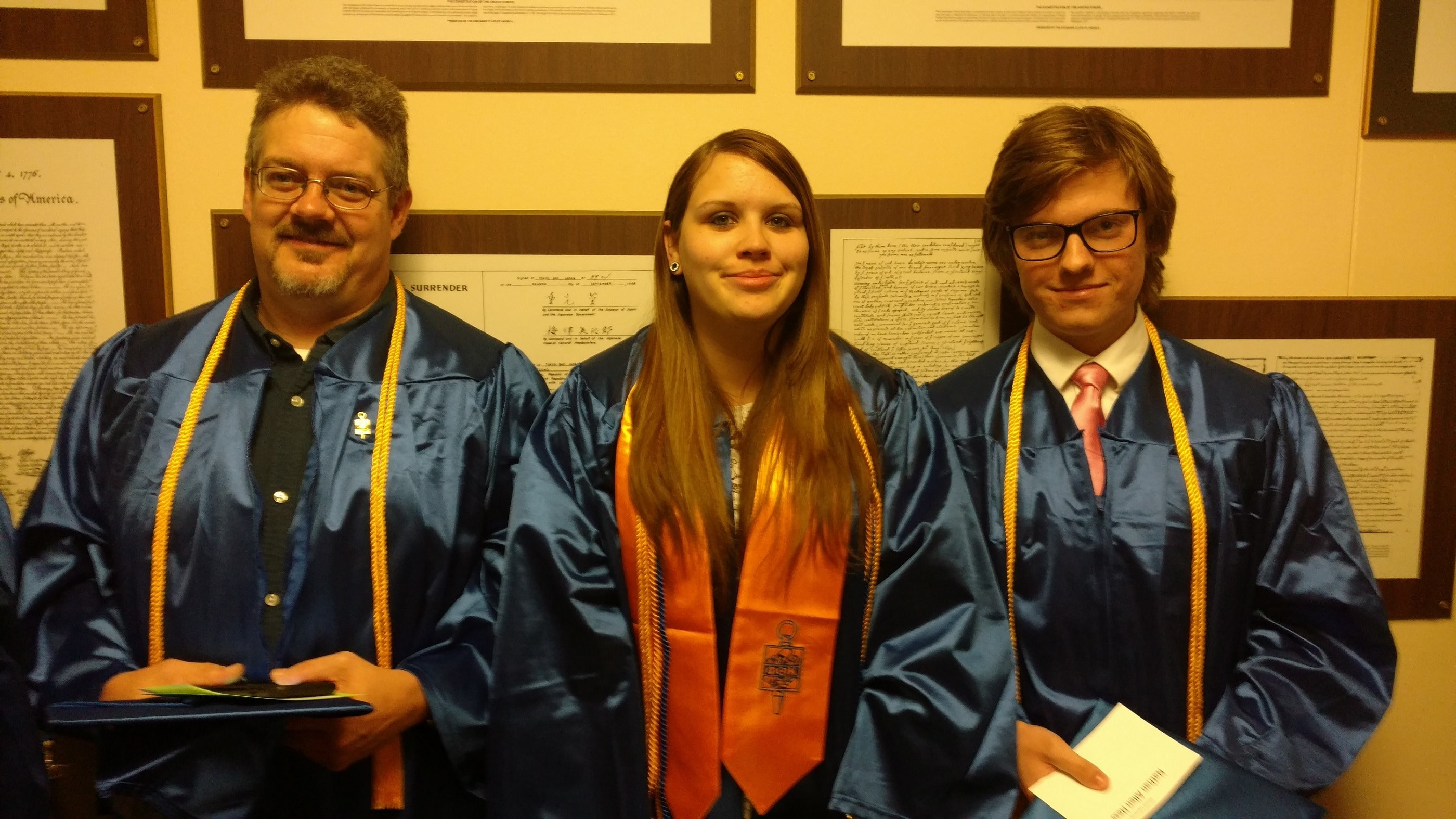 Three civil engineering students stand in graduation cap and gowns