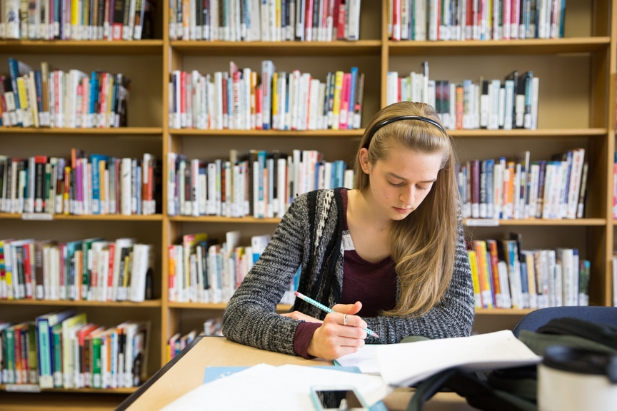Female student studies and writes in notebook in Moraine Park library