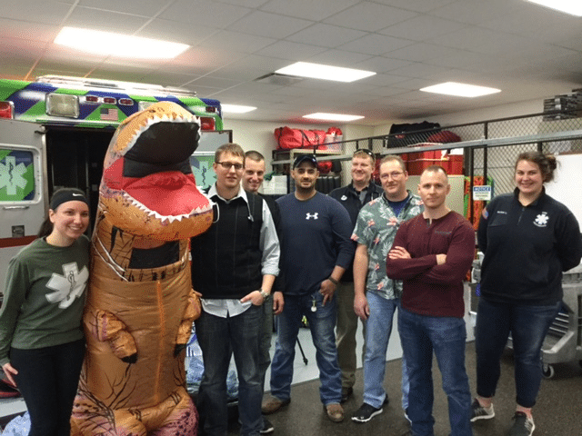 Moraine Park paramedic students standing with dinosaur costume