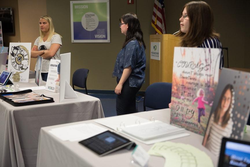 Three female Moraine Park students standing around portfolio tables