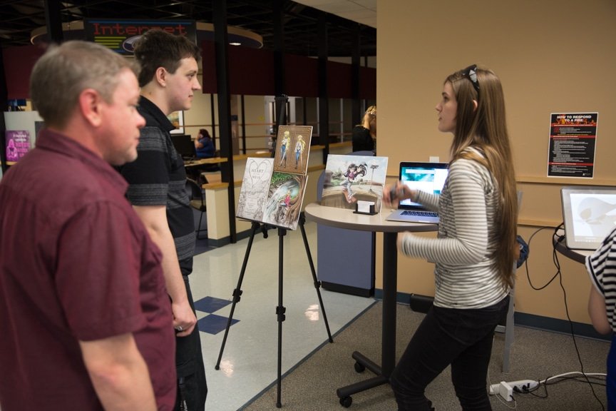 Female and two males looking at artwork at Moraine Park portfolio showcase.