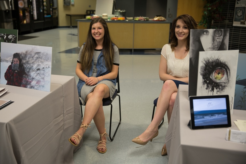 Two female Moraine Park students sitting around portfolio tables