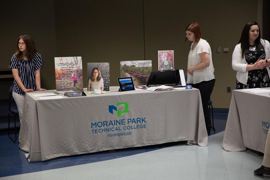 Moraine Park female students standing near portfolio table