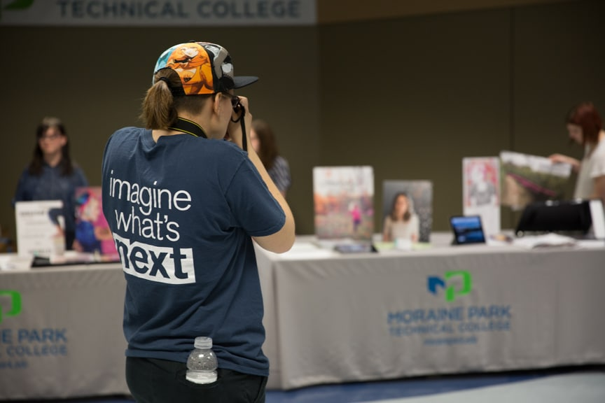 Moraine Park female student photographing portfolio tables