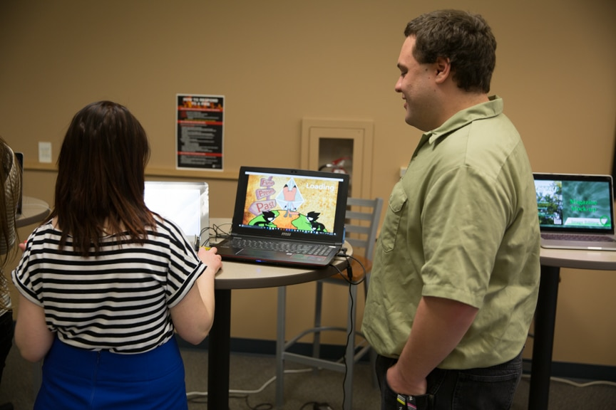Male and female students at Moraine Park working on a computer at portfolio showcase