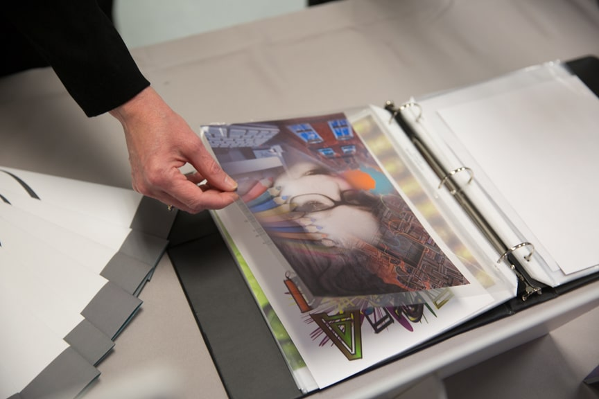 Portfolio of artwork in a binder on desk