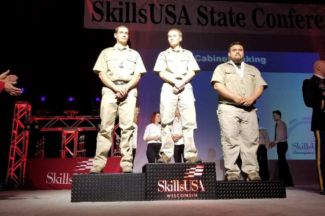 Three male MPTC SKills USA winners standing on stage