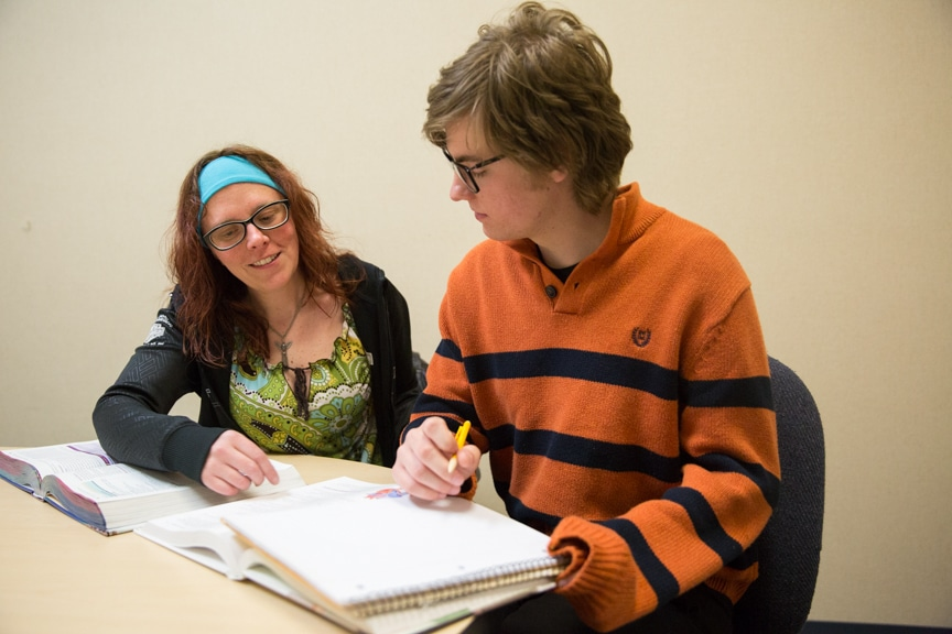Student tutor sitting with another student and books
